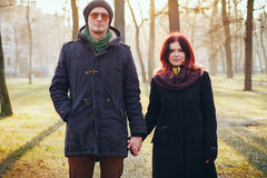 Young couple in love walking in the autumn park. Holding hands looking in the sunset Stock Images