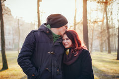 Young couple in love walking in the autumn park. Holding hands looking in the sunset Royalty Free Stock Photo