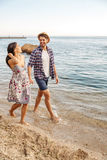 Young couple in love walking at the beach holding hands Royalty Free Stock Photos