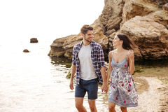 Young couple in love walking at the beach holding hands Stock Photo