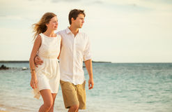 Young couple in love walking on the beach at sunset Royalty Free Stock Photo