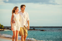 Young couple in love walking on the beach at sunset royalty free stock photos