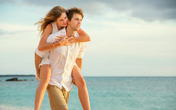 Young couple in love walking on the beach at sunset Royalty Free Stock Images