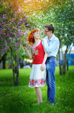 Young couple in love walking at the blossoming spring garden Royalty Free Stock Photo