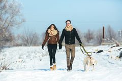 Young couple in love walking with dog Stock Photo