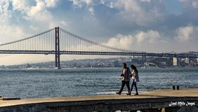 Young Couple In Love. Couple walking hand in hand on a pier in front of Lisbon`s Ponte 25th of April Bridge over the river Tagus Stock Image