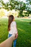 Young couple in love walking through meadow on sunny day. Young couple in love walking on sunny day and holding their hands Royalty Free Stock Photography