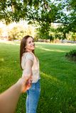 Young couple in love walking through meadow on sunny day. Young couple in love walking on sunny day and holding their hands Royalty Free Stock Images