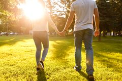 Young couple in love walking through meadow on sunny day. Young couple in love walking on sunny day and holding their hands Stock Images