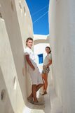 Young couple in love walking on narrow streets of. Young couple in love walking in the narrow streets of the village of Emporio, Santorini in Greece Royalty Free Stock Image