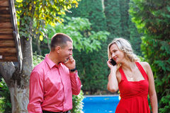 Young couple in love walking in the park and talking on the phone stock image