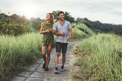 Young couple in love walking on pathway through grass field Stock Image