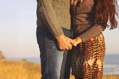 Young couple in love walking by the sea holding hand. At sunset time Stock Image