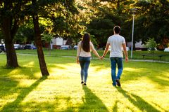 Young couple in love walking through meadow on sunny day. Young couple in love walking on sunny day and holding their hands Stock Photos