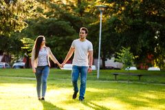 Young couple in love walking through meadow on sunny day. Young couple in love walking on sunny day and holding their hands Royalty Free Stock Photos