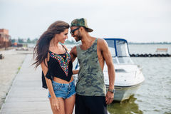 Young couple in love walking at the wooden sea pier. Happy young couple in love walking at the wooden sea pier Royalty Free Stock Photos