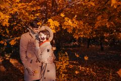 Young couple in love walks in autumn forest among falling leaves. Stylish people hugging. And chilling outdoors stock photo