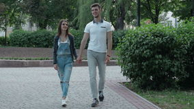 Young couple in love walks in the Park and hold hands stock footage