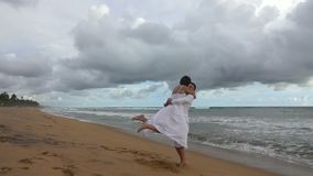 Young couple in love whirling and hugging on ocean beach at sunset stock video