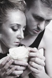 Young couple in love with a white rose Royalty Free Stock Image
