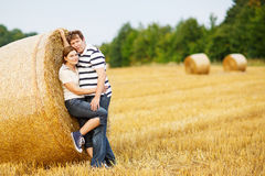 Young couple in love on yellow hay field on summer evening. Stock Photo
