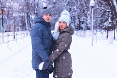 Young couple of lovers walk in winter park Royalty Free Stock Images