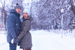 Young couple of lovers walk in winter park Royalty Free Stock Photography