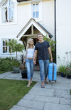 Young couple with luggage walking away from a house Royalty Free Stock Image