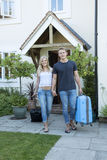 Young couple with luggage walking away from a house Stock Photo