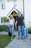Young couple with luggage walking away from a house Stock Photos