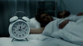 Young couple lying asleep in bed at night with clock standing near, sleep phases. Stock photo stock photos