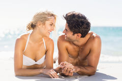 Young couple lying on beach. Happy young couple looking at each other and lying on beach Stock Images