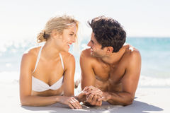 Young couple lying on beach. Happy young couple looking at each other and lying on beach Stock Photos