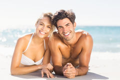 Young couple lying on beach. Portrait of happy young couple lying on beach Stock Photography
