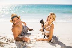 Young couple lying on beach stock photo