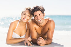 Young couple lying on beach. Portrait of happy young couple lying on beach Royalty Free Stock Images