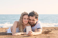 Young couple lying on the beach, using smart phone Royalty Free Stock Images