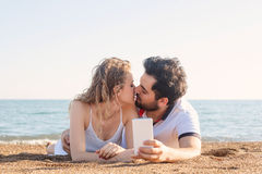 Young couple lying on the beach, using smart phone Stock Images
