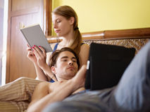 Young couple lying on bed Stock Images