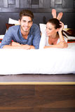 A young couple lying on the bed in an asian style hotel room Stock Images