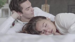 Upset offended girl ignoring boyfriend, turned away, misunderstanding, conflict. Young couple lying in bed close-up. Young couple lying in bed close-up. Girl stock video footage
