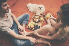 Young couple is lying in bed with dog. Royalty Free Stock Photos