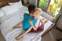 Young Couple Lying On Bed, Happy Smile Hispanic Man And Woman Embrace Bedroom Stock Image