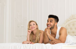 Young Couple Lying In Bed, Happy Smile Hispanic Man And Woman Lovers In Bedroom Stock Photo