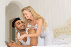 Young Couple Lying In Bed, Happy Smile Hispanic Man And Woman Using Cell Smart Phone Stock Photo