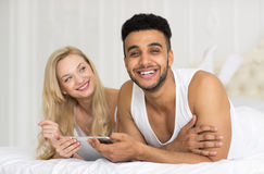 Young Couple Lying In Bed, Happy Smile Hispanic Man And Woman Using Tablet Computer Stock Images