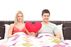 Young couple lying in bed and holding a red heart Stock Photo