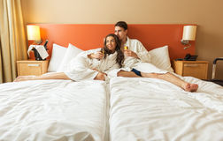 Young Couple lying in the bed of a hotel room Royalty Free Stock Photo