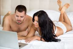 Young couple lying on bed with laptop Royalty Free Stock Photos