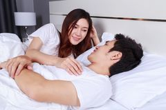 Young couple lying in a bed and looking to each other eyes to e Royalty Free Stock Image